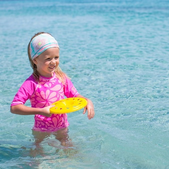 Little girl playing frisbee during tropical vacation in the sea