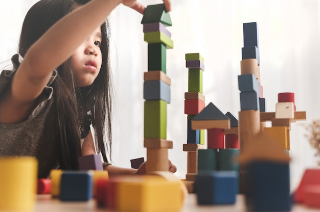 Маленькая девочка, играя в игру здание конструктор башня из разноцветных деревянных блоков. концепция обучения и развития.