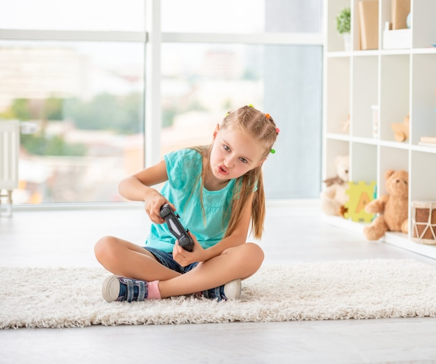 Little girl playing games with joystick