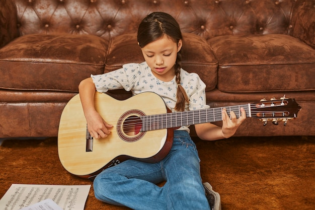 Little girl playing guitar at home