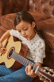 Bambina a suonare la chitarra a casa