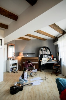 Маленькая девочка играет на гитаре с учителем музыки в деревенской квартире
