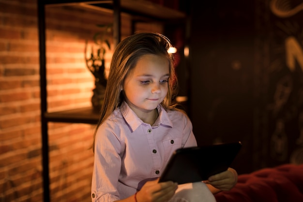 Little girl playing on her tablet