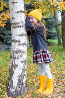 Little girl playing hide and seek in autumn forest outdoors