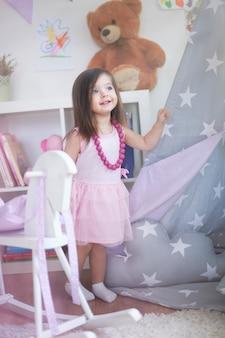 Маленькая девочка играет в своей комнате