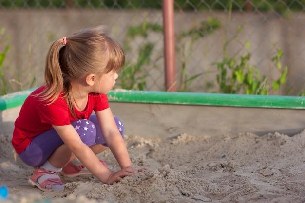 Маленькая девочка играет в песочнице в солнечный летний день
