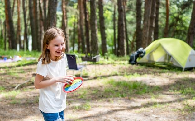 Маленькая девочка играет в кемпинге в лесу с зеленой палаткой на фоне красивый улыбающийся ребенок ч ...