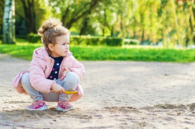 秋の日に公園の砂で遊ぶ少女。