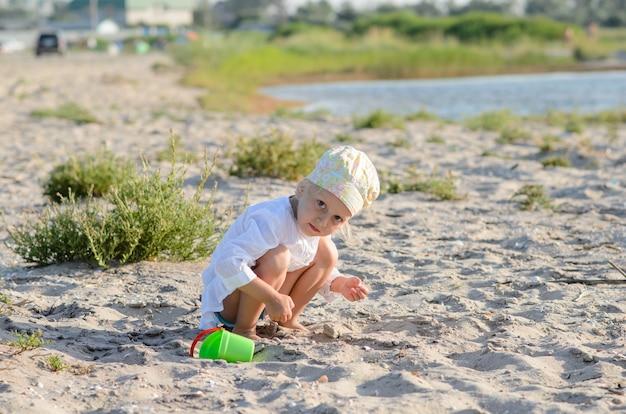 Маленькая девочка играет в песке у моря.