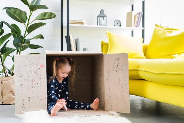 Little girl playing inside cardboard box