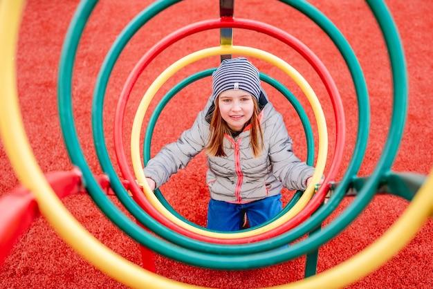 Маленькая девочка играет внутри металлической красочной спирали на детской площадке и улыбается
