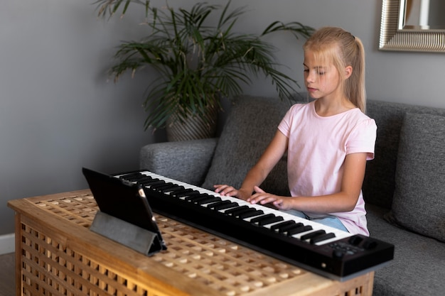Little girl playing keyboard at home