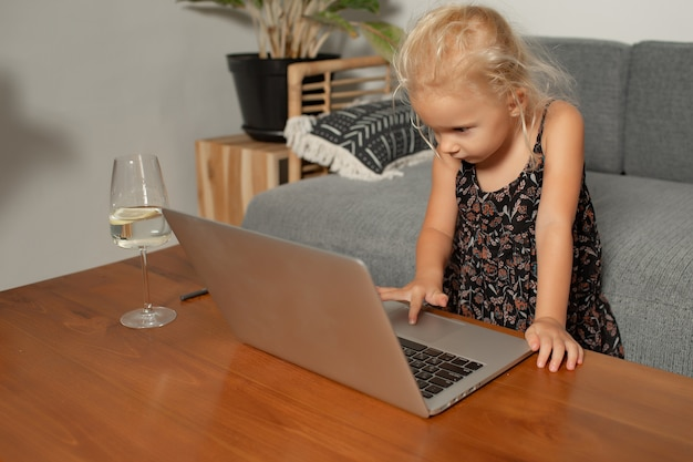 Little girl playing on laptop. high quality photo