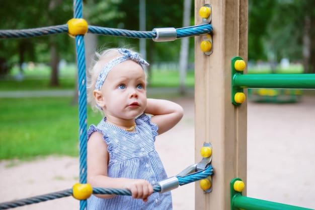 놀이터에서 밧줄 그물에 어린 소녀