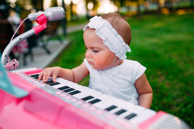 Маленькая девочка играет на игрушечном пианино в парке