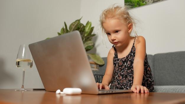 ラップトップで遊んでいる少女。高品質の写真