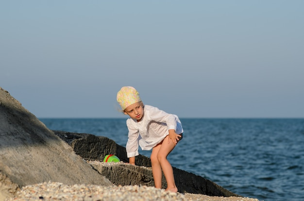 Маленькая девочка, играя на пляже.