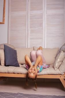 Маленькая девочка, играя на диване.