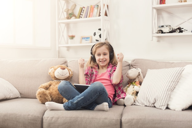 Little girl playing online games on digital tablet and listening to music in headphones. female child sitting on sofa with her toys. social networking and online education concept