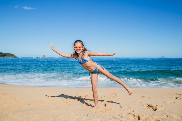 Little girl playing and posing on the beach