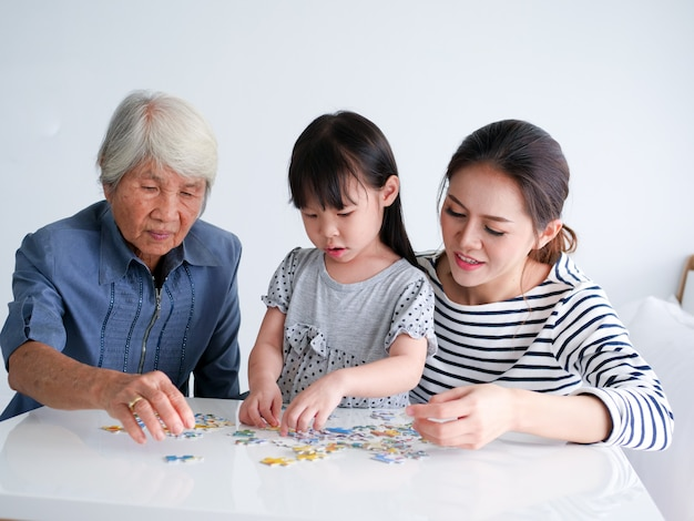 Little girl playing puzzel with her mother and grandmother at home on weekend.