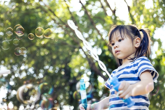Little girl playing soap bubble in playground.