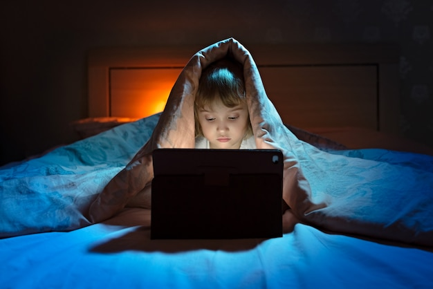 Little girl playing tablet under blanket at night
