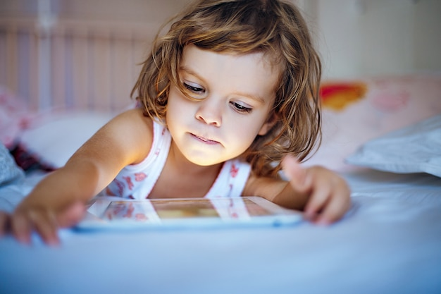 Little girl playing tablet