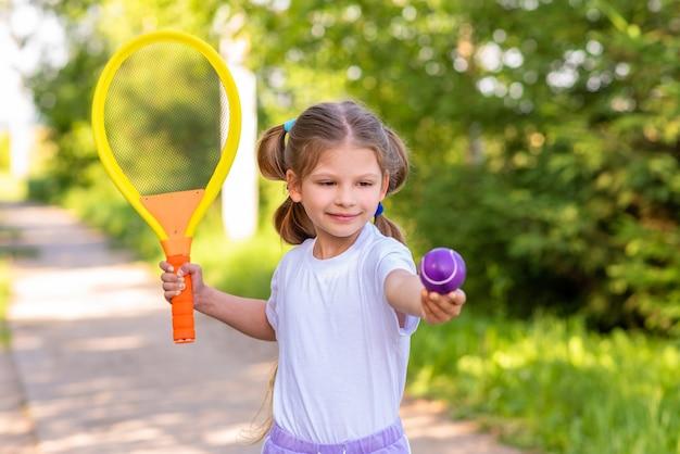 Маленькая девочка играет в теннис в парке.
