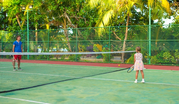 Little girl playing tennis with her dad on the court