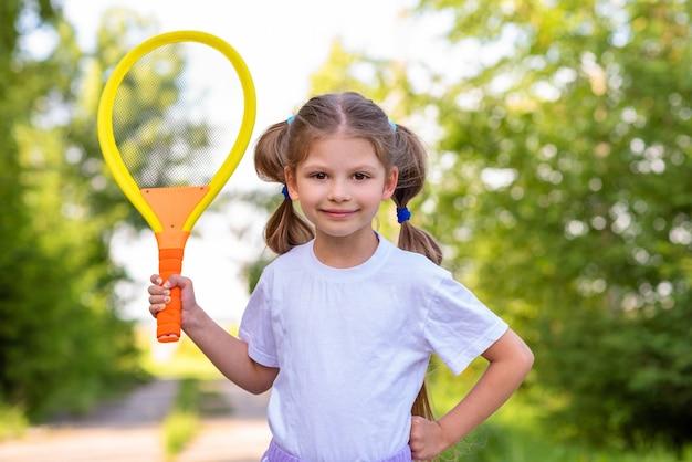 Маленькая девочка играет в теннис