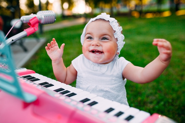 Little girl playing on a toy piano in the park