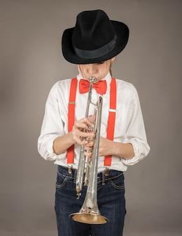 Маленькая девочка играет на трубе на сером