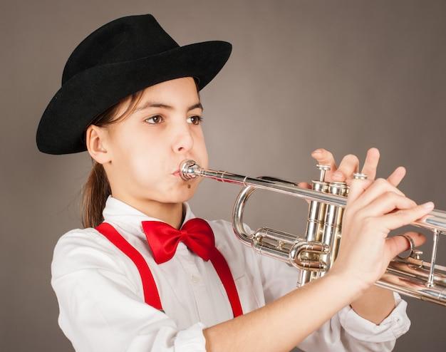 Маленькая девочка играет на трубе