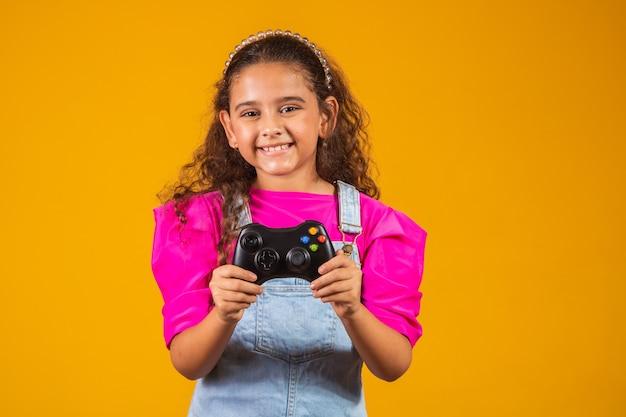 노란색 배경에서 비디오 게임을 하는 어린 소녀.