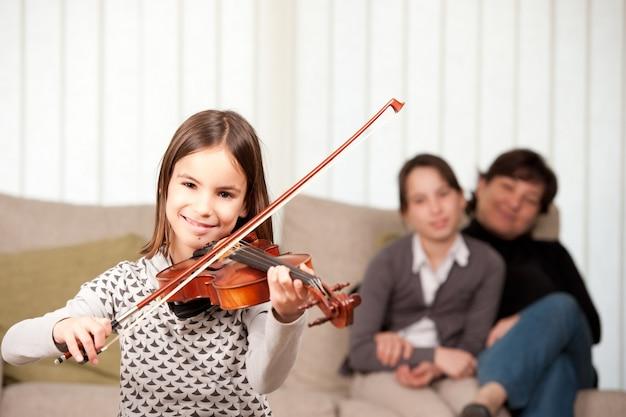 어린 소녀가 집에서 그녀의 가족과 함께 바이올린을 연주