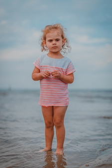 Little girl playing in the waves at sea