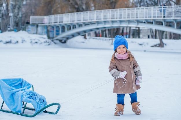 Маленькая девочка играет с санями в парке на фоне моста и замерзшего озера