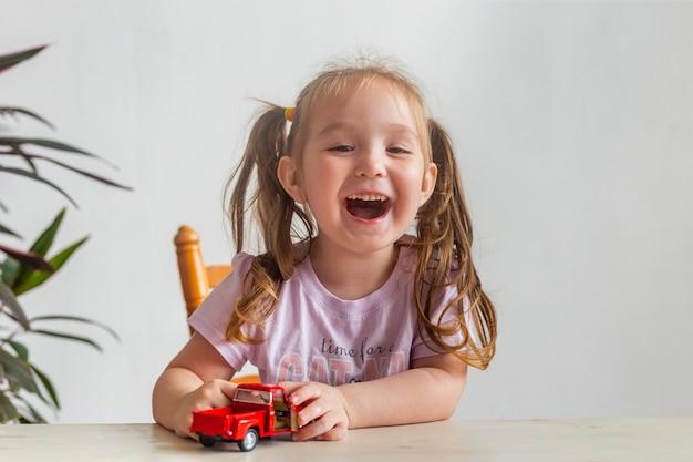Маленькая девочка играет с маленькой красной игрушечной машинкой