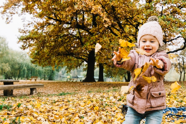 Little girl playing with autumn leaves in park