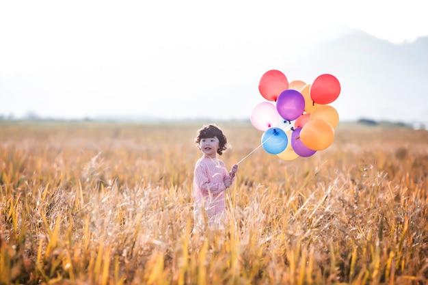 밀밭에 풍선을 가지고 노는 어린 소녀