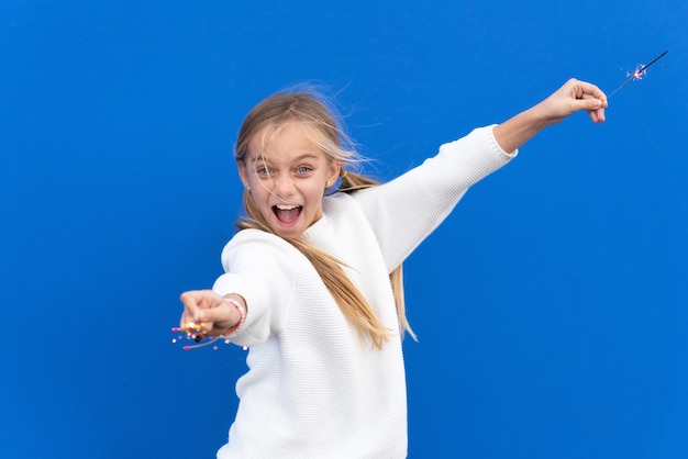 Little girl playing with bengal lights on blue background