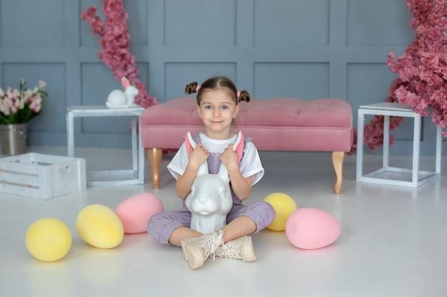 Маленькая девочка играет с кроликом маленький фермер ребенок в комбинезоне сидит на полу и играет