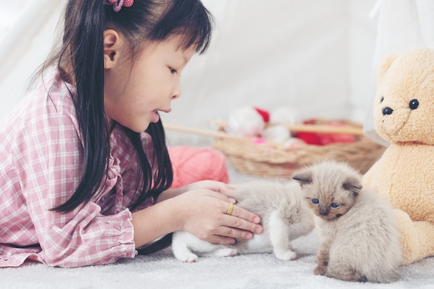 Little girl playing with cat at home, friend ship concept.