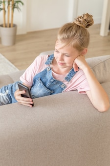 Little girl playing with a cell phone at home on a couch
