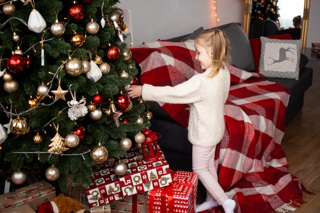 Little girl playing with christmas tree decoration at home