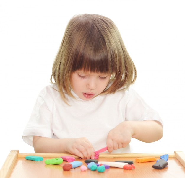 Little girl playing with clay on white.