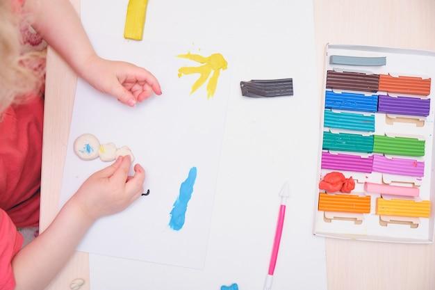 Маленькая девочка играет с красочной лепкой на столе. игра для домашнего образования с глиной. концепция раннего развития ребенок лепит из пластилина