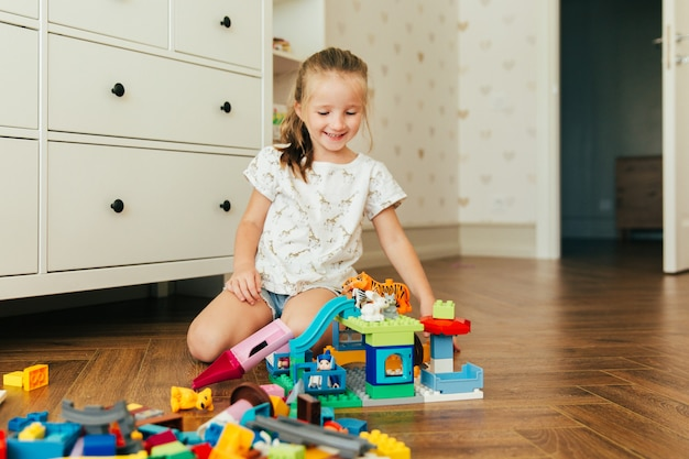 Little girl playing with colorful toy blocks. educational and creative toys and games for young children. playtime and mess in kid's room