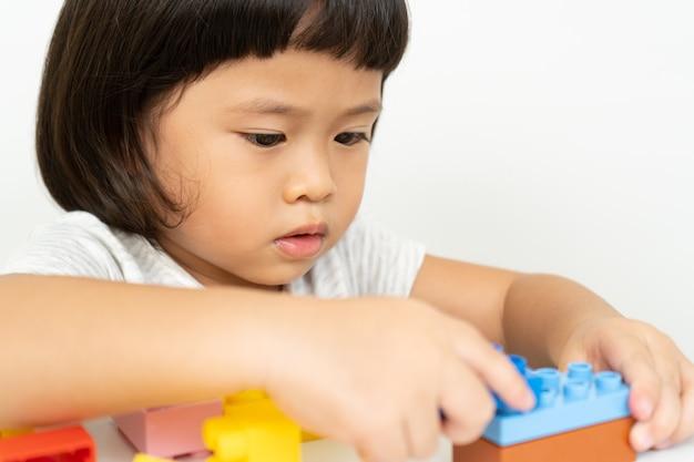 白のカラフルなおもちゃのブロックで遊ぶ小さな女の子、子供たちは教育的なおもちゃで遊ぶ